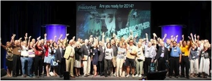 Speakers and attendees hold up silver dollars at FreedomFest (July 2014).