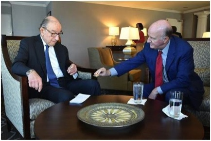 Mark Skousen shows Alan Greenspan an American eagle silver dollar. Although he is a collector of old Morgan and Peace silver dollars, he said he had never seen an American eagle silver dollar. (New Orleans conference, October 2014).